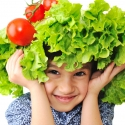 Kid with salad and tomato hat on his head, fake hair made of vegetables